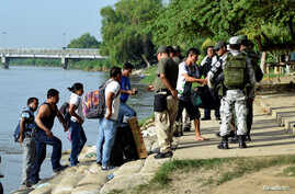 FILE - Members of Mexico's National Guard check people crossing the Suchiate river on a raft from Tecun Uman, Guatemala, to Ciudad Hidalgo, as seen from Ciudad Hidalgo, Mexico, July 3, 2019.