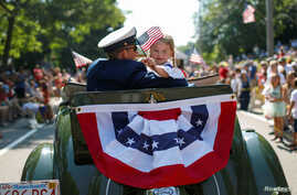 A man and a girl ride in an antique Ford automobile during the annual 4th of July parade in Barnstable Village on Cape Cod, Massachusetts, July 4, 2019.