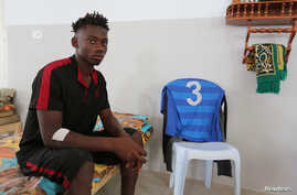 An African migrant who a government source said was rescued after the boat he was traveling in capsized in the Mediterranean Sea off the Tunisian coast, sits inside a local Red Crescent chapter in Zarzis, Tunisia, July 4, 2019.