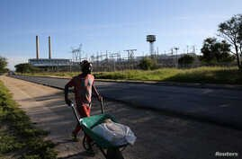 FILE - A man pushes a wheelbarrow past Namibia's power utility Nampower in Windhoek, Namibia.