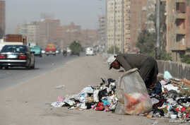 FILE - A man picks through rubbish on a road in Cairo, Egypt, Oct. 29, 2018.