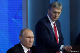 FILE - Kremlin spokesman Dmitry Peskov listens as Russian President Vladimir Putin speaks during annual news conference in Moscow, Russia, Dec. 20, 2018.