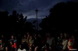 FILE - With the streetlight dark, Haitians watch the screening of a friendly soccer match between Chile and Haiti, at Jean-Jacques Dessalines square in Port-au-Prince, Haiti, June 6, 2019.