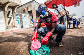 A health worker wearing protective gear mixes water and chlorine in Goma, DRC, July 31, 2019.