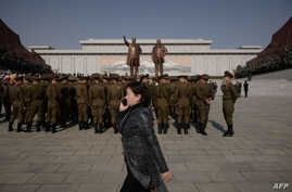 A woman talks on a mobile phone as Korean People's Army soldiers gather for a memorial tribute before the statues of late North Korean leaders Kim Il Sung and Kim Jong Il, on Mansu hill in Pyongyang, North Korea, April 15, 2019.
