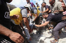 Syrian rescuers and civilians pull a man from the rubble of a building following an airstrike by regime forces in Maar Shurin on the outskirts of Maaret al-Numan in northwest Syria, July 16, 2019.