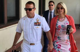 Navy Special Operations Chief Edward Gallagher, left, walks with his wife, Andrea Gallagher as they arrive to military court on Naval Base San Diego, July 1, 2019, in San Diego.