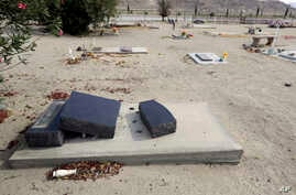Fragments of a headstone are seen after tumbling over onto a grave in the aftermath of an earthquake at Searles Valley Cemetery, in Trona, California, July 7, 2019.