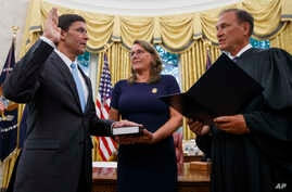 Mark Esper, left, is sworn in as Secretary of Defense by Supreme Court Justice Samuel Alito, right, as his wife Leah Esper holds the Bible, during a ceremony with President Donald Trump in the Oval Office at the White House in Washington, July 23, 2019.