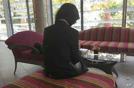 FILE - Grace Meng, the wife of former Interpol President Meng Hongwei consults her mobile phone in the lobby of an hotel in Lyon, central France, Oct. 7, 2018.