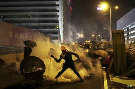 A protester throws a tear gas canister which was fired by riot police during a rally in Hong Kong, July 28, 2019.