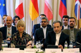 The European Union's Political Director Helga Schmid, front left, and Iran's Deputy Foreign Minister Abbas Araghchi, front right, attend meeting held as part of closed-door nuclear talks with Iran, at a hotel in Vienna, Austria, July 28, 2019.