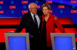 Sens. Bernie Sanders, left, and Sen. Elizabeth Warren embrace after the first of two Democratic presidential primary debates hosted by CNN in Detroit, July 30, 2019.