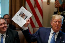 Secretary of State Mike Pompeo, left, looks at a paper held by President Donald Trump about Rep. Ilhan Omar, D-Minn., as Trump speaks during a Cabinet meeting in the Cabinet Room of the White House, Tuesday, July 16, 2019, in Washington.