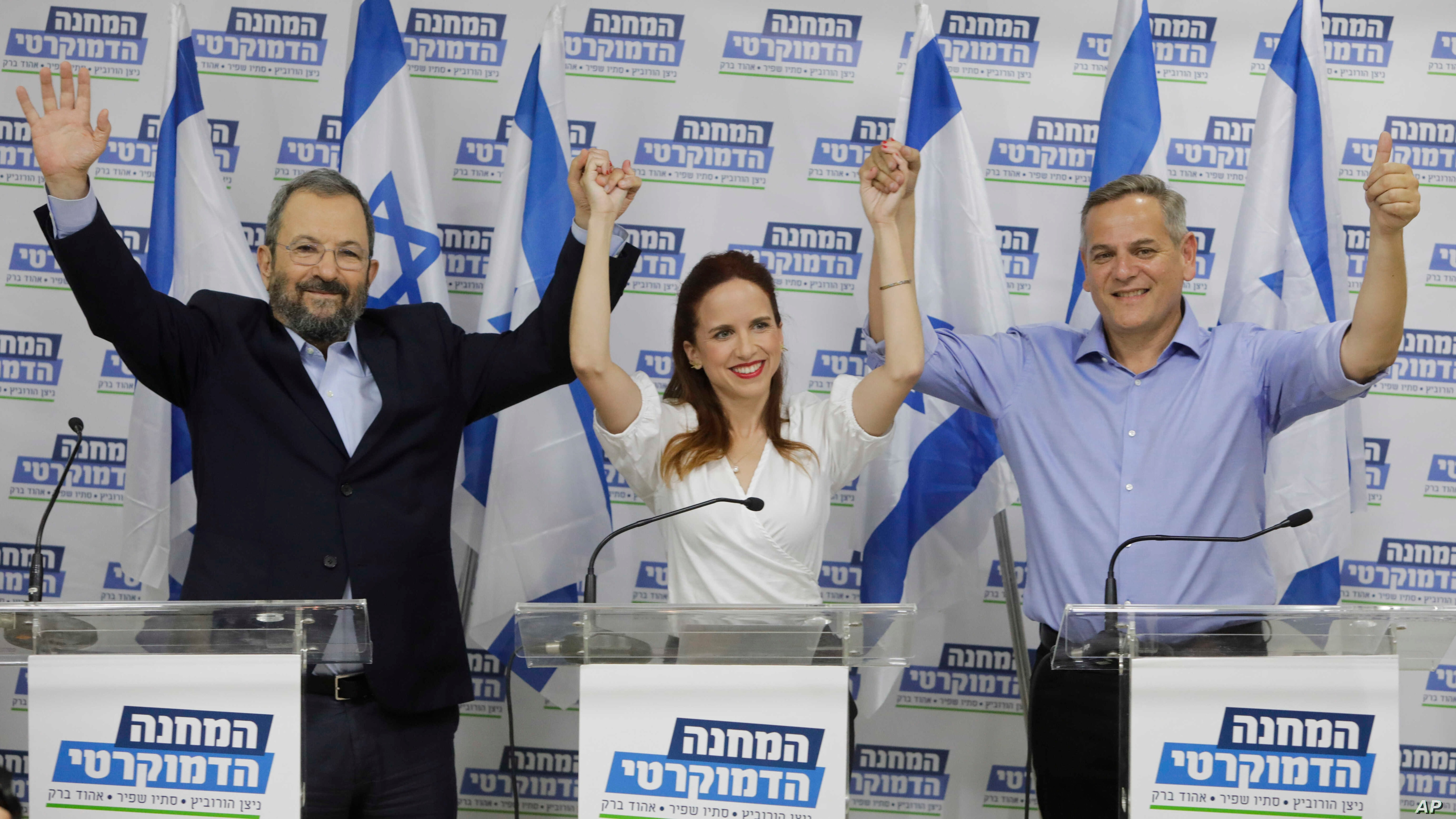 """Ehud Barak, left, Tamar Zandberg, and Stav Shaffir. raise hands after they announced their joint faction """"The Democratic Camp"""" for the upcoming elections in Israel, in Tel Aviv, Thursday, July 25, 2019."""