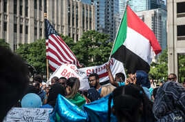 Protesters hold American and Sudanese flags at a rally in support of the Sudan's revolution, in Chicago, Illinois, June 29, 2019. (J. Patinkin/VOA)