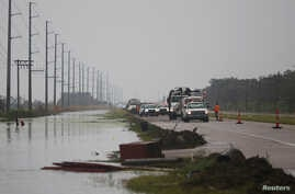Crews clear debris from Highway 23 during storm Barry in Plaquemines Parish, Louisiana, July 14, 2019. Barry was first billed as a hurricane, and then downgraded, first to a tropical storm, and then to a tropical depression.