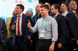 Ukrainian President Volodymyr Zelenskiy, center, reacts with his team as they look at the election results at his party's headquarters after a parliamentary election in Kiev, Ukraine, Sunday, July 21, 2019.