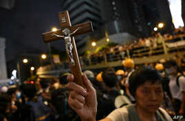 A protester holds a Christian cross as others gather outside the police headquarters in Hong Kong, June 21, 2019.