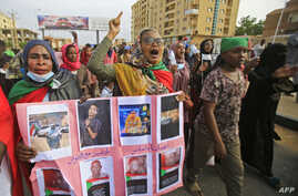 Sudanese women hold a banner bearing pictures of killed protesters during a demonstration called for by the Sudanese Professionals Association (SPA) to denounce the July 29 Obeid killings, in the capital Khartoum on Aug. 1, 2019.