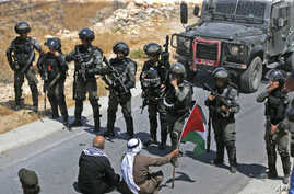Palestinian protesters sit before Israeli troops during a demonstration against the expropriation of Palestinian land by Israel, in the village of Kafr Malik northeast of Ramallah in the Israeli-occupied West Bank.