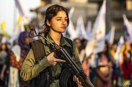 A member of the Kurdish Internal Security Police Force of Asayish stands guard as Syrian Kurdish demonstrate against Turkish threats to invade the Kurdish region, in the northeastern city of Qamishli, Aug. 27, 2019.