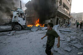 A boy runs past a fire started in a building following a reported airstrike by Syrian regime forces in the town of Maaret al-Numan in Syria's northwestern Idlib province, Aug. 28, 2019.
