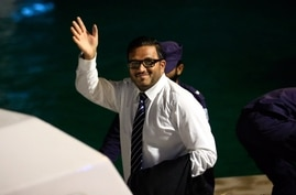 Former Maldives vice president Ahmed Adeeb waves to the media before he boards a police speed boat in Maldives, June 10, 2015.