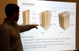 In this Nov. 15, 2016, file photo, engineer Eric McDonnell shows diagrams of skyscraper construction using cross-laminated timber in Portland, Oregon. City officials have approved a construction permit for the first all-wood high-rise building in the nation.