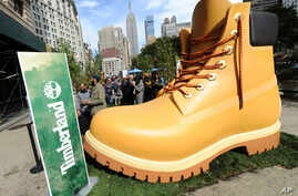 FILE - Timberland drops a 13-foot replica of its iconic wheat boot at a pop-up park in New York City, Oct. 16, 2018.