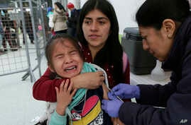 A Venezuelan girl cries while receiving a measles vaccine at an immigration processing office on the Rumichaca bridge, after crossing the border from Colombia to Ecuador, June 13, 2019.