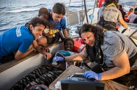 Doctors tend to a pregnant woman on a Mediterranea Saving Humans NGO boat, as they sail off Italy's southernmost island of Lampedusa, just outside Italian territorial waters, on Thursday, July 4, 2019.