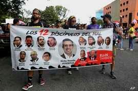 Protesters demanding the resignation of Justice Secretary Wanda Vazquez hold a banner featuring resigned Gov. Ricardo Rossello(C)and other politicians that reads in Spanish 'The 12 disciples of evil. Them too', San Juan, Puerto Rico, July 29, 2019.