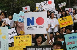 South Korean protesters hold up cards calling for a boycott of Japanese products during a rally demanding full compensation and an apology for wartime sex slaves from Japan in front of the Japanese Embassy in Seoul, South Korea, July 31, 2019.