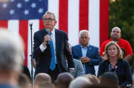 FILE - Ohio Gov. Mike DeWine, left, speaks during a vigil at the scene of a mass shooting in Dayton, Ohio, Aug. 4, 2019.