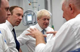 Britain's Prime Minister Boris Johnson, center, visit Pilgrim Hospital in Boston, northeast England, Aug. 5, 2019.