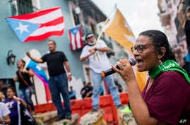 Protesters gather outside the government mansion La Fortaleza in San Juan, Puerto Rico, Wednesday, Aug. 7, 2019, calling for the removal of the island's newly sworn-in governor.