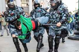 Police detain a man during a protest in Moscow, Aug. 10, 2019. Thousands rallied against the exclusion of some city council candidates from Moscow's upcoming election, turning out for one of the capital's biggest political protests in years.