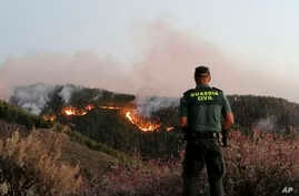 In this photo issued by the Guardia Civil, an officer looks at a forest fire in Gran Canaria, Spain, Aug. 11, 2019.
