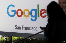 FILE - A person walks past a Google sign in San Francisco, May 1, 2019.
