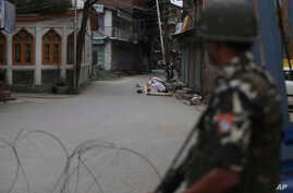 An Indian paramilitary soldier stands guard as Kashmiri Muslims offer Friday prayers on a street outside a local mosque during curfew like restrictions in Srinagar, India, Aug. 16, 2019.
