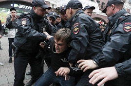 Police detain an activist during a protest in the center of Moscow, Russia, Saturday, Aug. 17, 2019. People rallied Saturday against the exclusion of some city council candidates from Moscow's upcoming election.