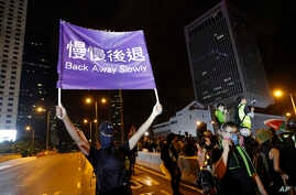 "A demonstrator holds up a sign reading ""Back away slowly"" to encourage other demonstrators to leave, near the Chinese Liaison Office in Hong Kong, Sunday, Aug. 18, 2019."