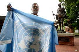 Lewis Randa, of Duxbury, Mass., displays a United Nations flag while standing near a bronze statue of Indian independence leader
