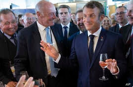 French President Emmanuel Macron, right, samples local produce and wine as he tours the exhibition hall on the opening day of th