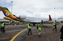 FILE - In this Tuesday, April 23, 2019 file photo, cameramen film at a ceremony to mark the arrival of two CRJ-900 jets from Canadian aerospace company Bombardier, at the airport in Entebbe, Uganda.