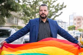 LGBT activist Mounir Baatour holds a rainbow flag after submitting his candidacy for the upcoming early presidential elections in Tunis, Tunisia, Aug. 8, 2019.