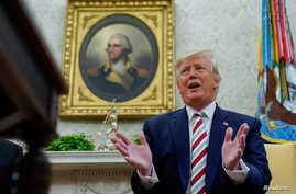 U.S. President Donald Trump answers questions from reporters sitting in front of a portrait of former U.S. President George Washington in the Oval Office of the White House in Washington, Aug. 20, 2019.