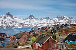 FILE PHOTO: Snow covered mountains rise above the harbor and town of Tasiilaq, Greenland, June 15, 2018.