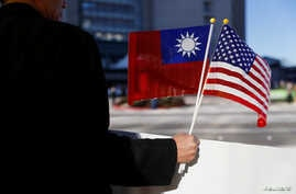 A demonstrator holds flags of Taiwan and the United States in support of Taiwanese President Tsai Ing-wen in Burlingame, California, Jan. 14, 2017.